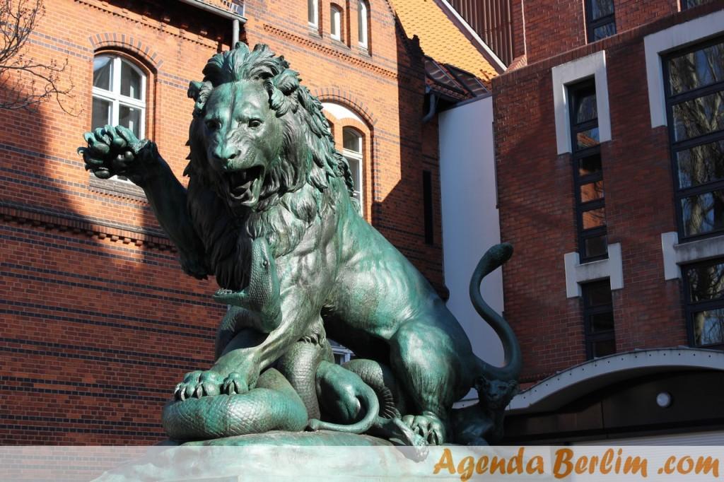 Escultura leão lutando contra cobra